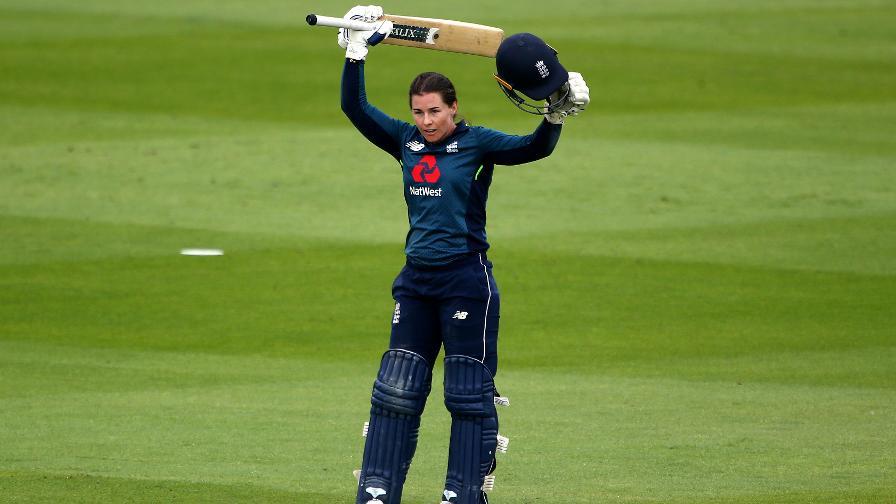 Tammy Beaumont raises her bat after reaching triple figures