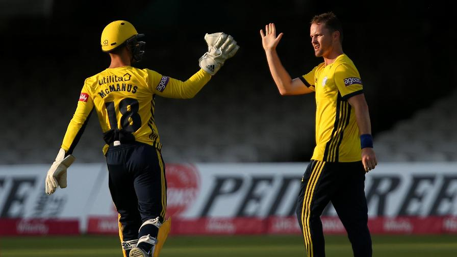 Colin Munro high-fives wicket-keeper Lewis McManus after taking the wicket of key man Paul Stirling